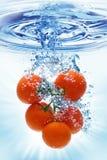 Het bespatten van de tomaat in water Stock Foto's