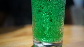 Het bespatten van groene kola met bellen in een glas die zich op een lijst in langzame motie bevinden stock videobeelden