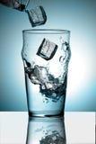 Het bespatten van het ijs in een glas water Royalty-vrije Stock Afbeelding