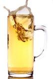 Het bespatten van het ijs in een mok bier Stock Foto