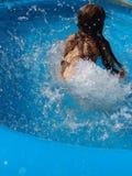 Het Bespatten van het meisje rond in de pool Stock Afbeeldingen