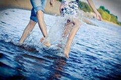 Het bespatten van het paar bij het strand Stock Fotografie