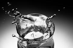 Het bespatten van het water uit een glas Stock Fotografie