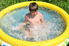 Het bespattende water van de jongen Stock Fotografie