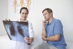 Het bespreken van röntgenstraal met patiënt stock afbeeldingen