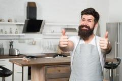 Het beste à la carte menu Gebaarde mannelijke kok die duimen UPS geven en restaurantmenu aanbieden Gelukkige ongeveer opgewekte h stock foto