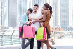 Het beste dag winkelen De mooie meisjes in kleding koesteren de kerel terwijl Stock Afbeeldingen