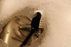 Het bestek en een schotelborstel liggen in een keukengootsteen met water en schuim wordt gevuld dat stock afbeelding