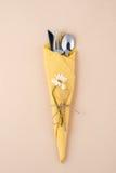 Het bestek is verpakt en verfraaid in een geel servet met cha Royalty-vrije Stock Fotografie