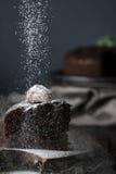 Het bestrooien van donkere chocoladecake met gepoederde suiker Stock Foto