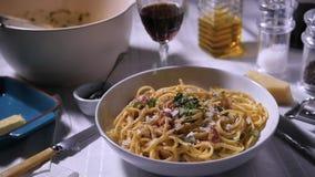 Het bestrooien van peterselie over een plaat van spaghetticarbonara, langzame motie stock videobeelden