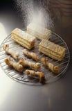Het bestrooien van suikerglazuursuiker over de gebakjes Stock Fotografie