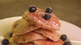 Het bestrooien van suikerglazuursuiker over pannekoeken echte Canadese ahornstroop, Middelgroot schot stock footage