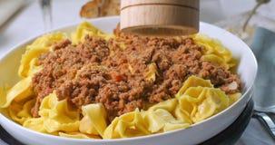 Het bestrooien van zwarte peper over heerlijke tortellini in bolognese saus Royalty-vrije Stock Afbeeldingen