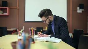 Het bestuderen van een jonge mens, herschrijft een notitieboekje stock video