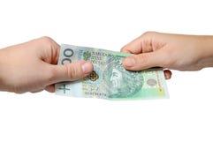 Het betalen met poetsmiddelmunt - pln Stock Fotografie