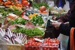Het betalen van kruidenierswinkels bij markt Stock Fotografie