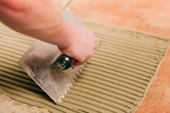 Het betegelen van de tegelzetter tegels op de vloer Stock Foto