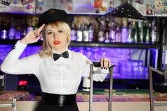 Het betoverende blondemeisje in zwart een hoogtepunt bereikt GLB zit Royalty-vrije Stock Foto's