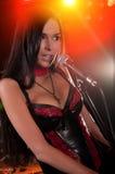 Het betoverende brunnetmeisje zingen op het stadium Stock Foto's