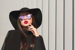 Het betoverende donkerbruine model in spiegelglazen en breed brimmed hoed Stock Foto