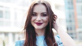 Het betoverende Europese donkerbruine meisje kijkt aan de camera, en glimlacht cutely, windspelen met haar haar, raakt zij het ha stock footage