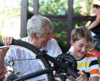 Het bevestigen van de jongen en van de grootvader fiets Stock Afbeelding