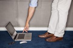 Het bevindende proberen van de mens om laptop in bureau te bereiken royalty-vrije stock afbeelding