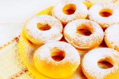 Het bevriezen van eigengemaakte donuts op gele plaat Stock Foto