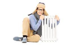 Het bevriezen van jonge kerel in van de de winterhoed en sjaal zitting naast radia Royalty-vrije Stock Foto