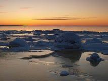 Het bevriezen van overzeese kust in het romantische avondlicht Stock Foto's