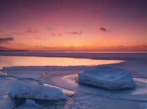 Het bevriezen van overzeese kust in het romantische avondlicht Stock Afbeelding
