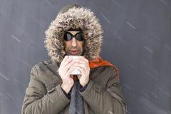 Het bevriezende de winteravonturier drinken van een metaalkop stock foto