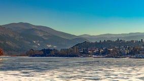 Het bevroren die meer met sneeuw wordt behandeld, mooie bergen kan in de afstand worden gezien royalty-vrije stock afbeeldingen