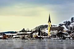 Het bevroren meer 'Schliersee 'in Beieren, Duitsland, in de winter met gele kerk St Sixtus en huizen met sneeuw in de rug royalty-vrije stock afbeelding