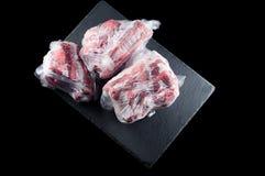 Het bevroren vlees in een plastic zak op een steentribune op een zwarte achtergrond, isoleert royalty-vrije stock afbeeldingen