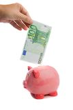 Het bewaren van een nota van honderd euro in een piggy-bank Stock Afbeeldingen