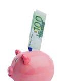 Het bewaren van een nota van honderd euro in een piggy-bank Stock Foto's