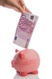 Het bewaren van een nota van vijf honderd euro in een piggy-verbod Stock Foto