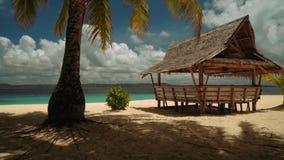 Het bewegen van afgelopen houten paviljoen onder palmen aan wit zandstrand stock footage