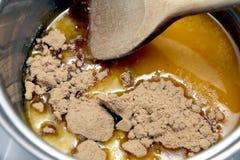Het bewegen van bruine suiker in gesmolten boter in een pan op de haardplaat stock foto's