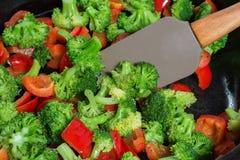Het bewegen van gestoofde groenten, in een pan, vegetarische keuken Stock Foto's