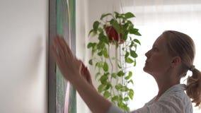 Het bewegen zich aan een nieuw huis Een jonge blondevrouw die een beeld op canvas in een ruimte bepalen stock footage
