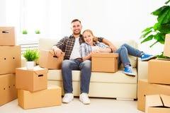 Het bewegen zich aan een nieuwe flat Gelukkige familiepaar en kartondoos stock afbeelding