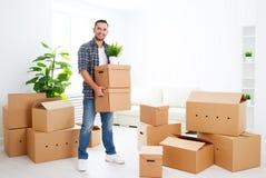 Het bewegen zich aan een nieuwe flat gelukkige mens met kartondozen stock fotografie