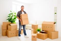 Het bewegen zich aan een nieuwe flat gelukkige mens met kartondozen stock foto's