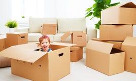 Het bewegen zich aan nieuwe flat gelukkig kind in kartondoos Stock Fotografie