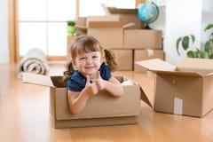 Het bewegen zich aan nieuwe flat gelukkig kind in kartondoos royalty-vrije stock foto