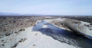 Het bewegen zich achteruit vanaf rivierbed in de herfst of de winter Openlucht zonnige aard scape over rivierbed dichtbij boswild stock video