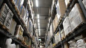 Het bewegen zich tussen pallets met goederen op planken